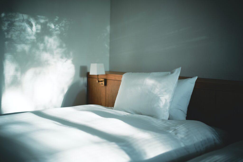 white bed linen beside brown wooden nightstand
