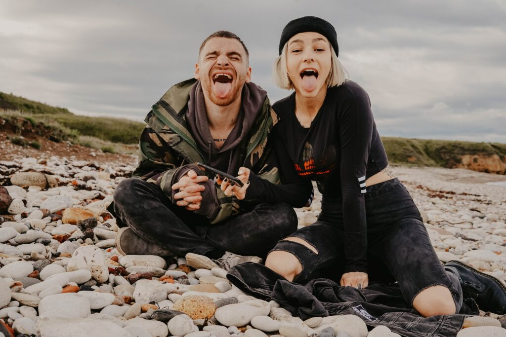 man and woman on stone field showing tongues during daytime