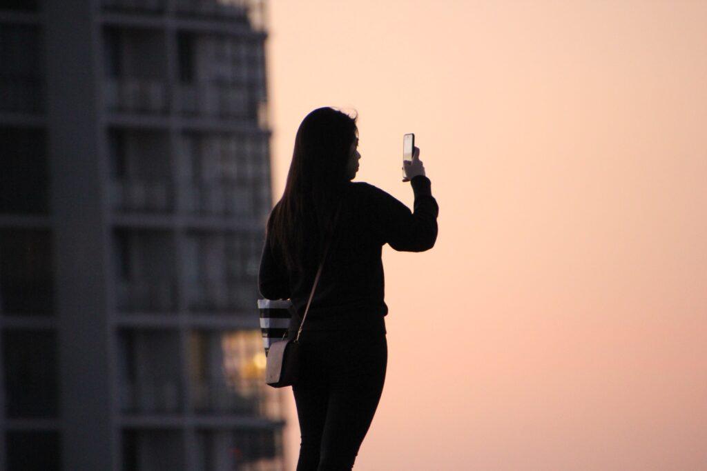 woman in black top using smartphone