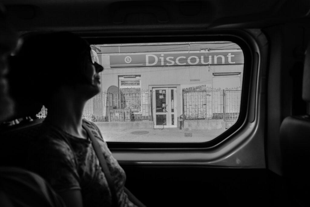 greyscale photography of woman inside vehicle