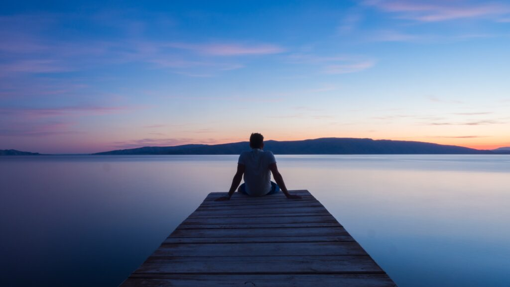man siting on wooden dock