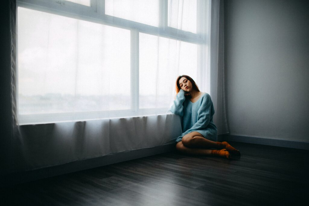 woman sitting on floor near window