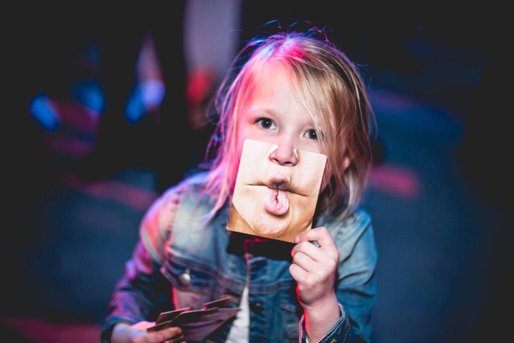 child holding photo of lips