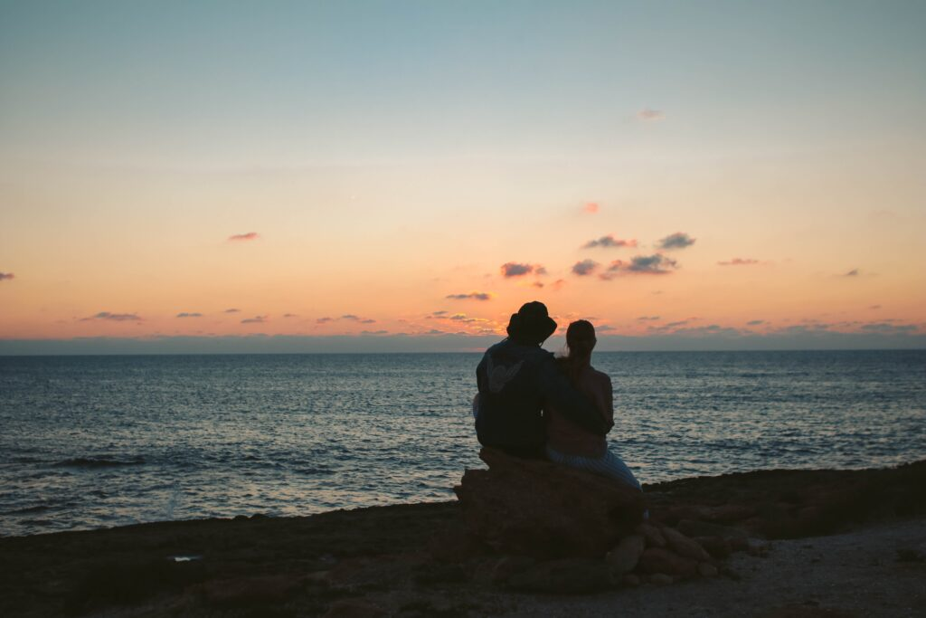 silhouette of couple sitting on rock at shore during golden hour
