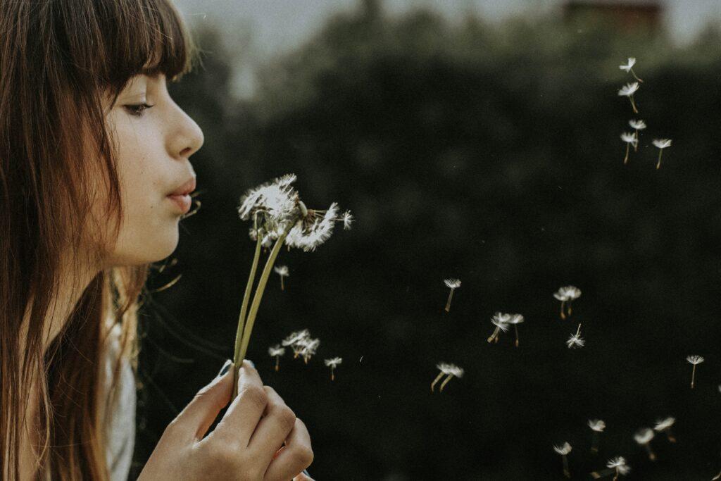 woman blowing dandelions