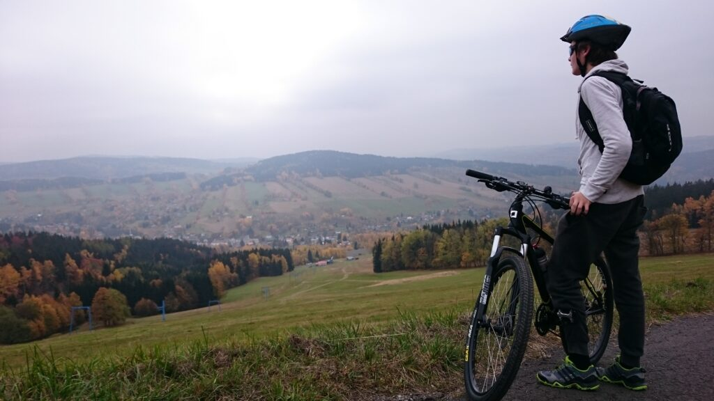 man standing on road with bicycle facing mountain range
