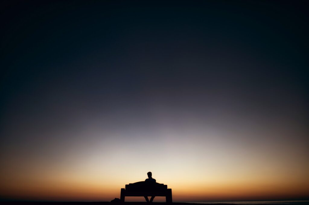 man sitting on bench facing sunset