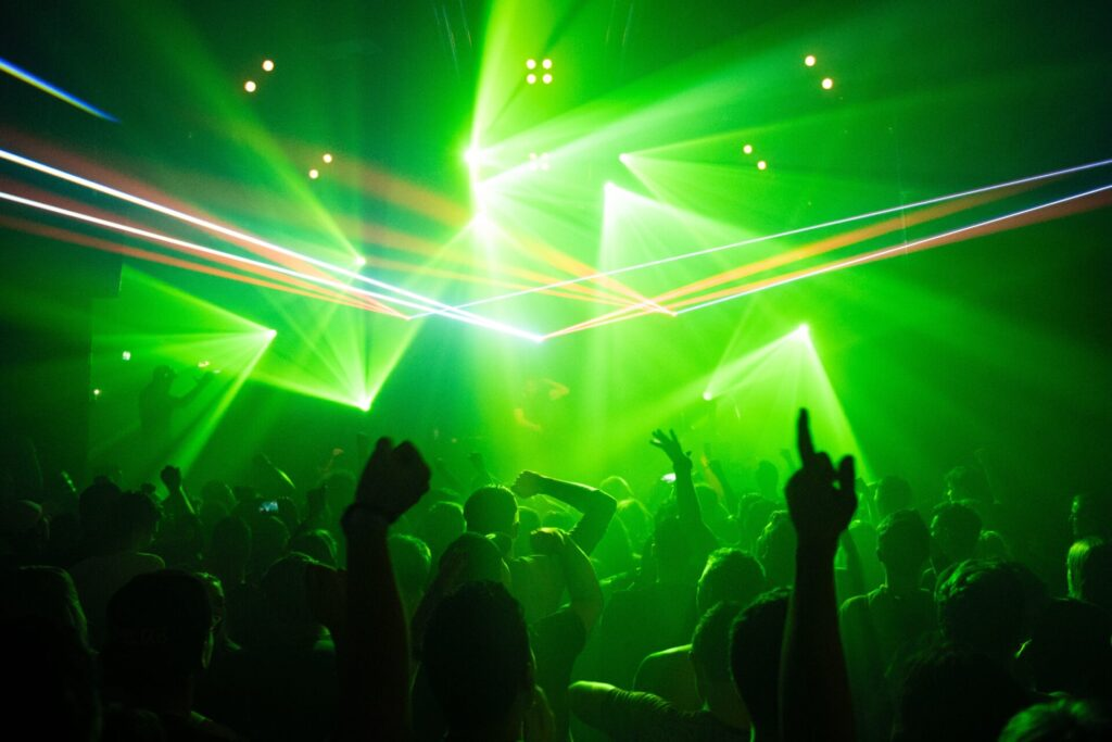 people dancing inside room with green lights