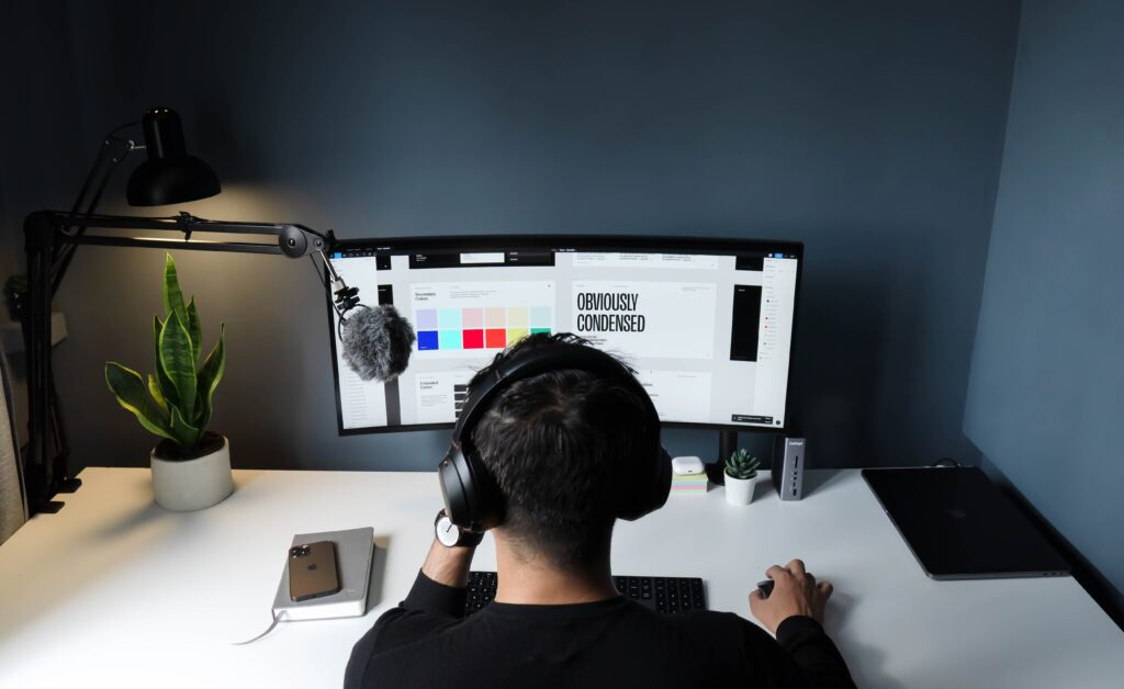 man in black shirt sitting in front of computer