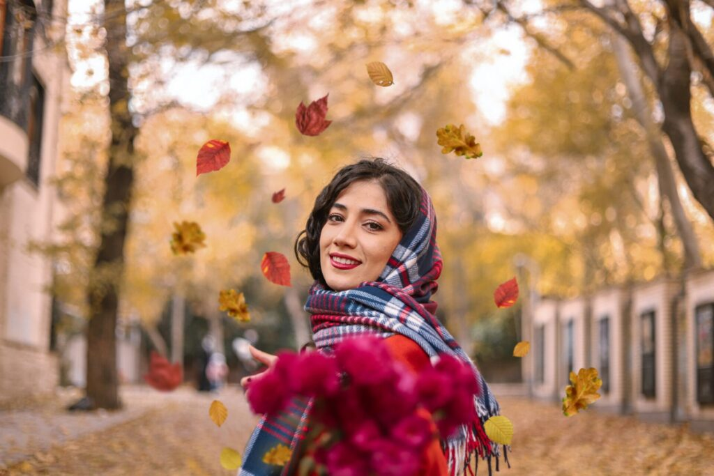 girl in red and white plaid scarf standing under red flowers