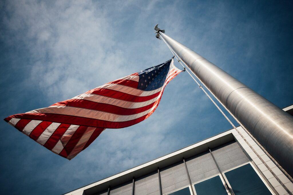 low-angle photo of U.S. flag placed on gray pole