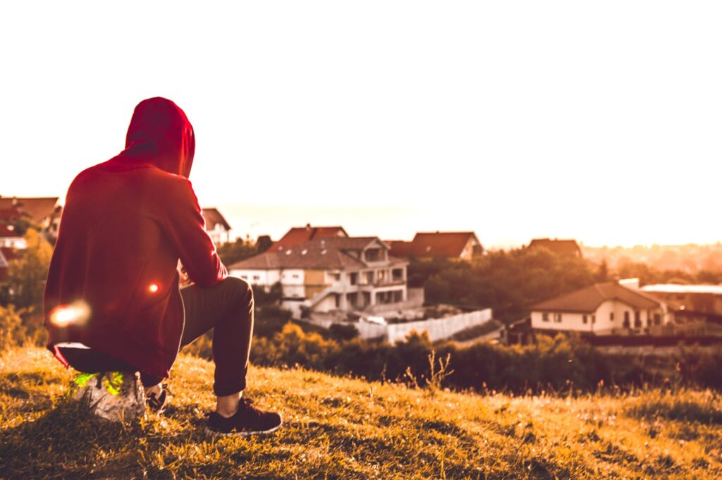 person sitting in hill near houses during daytime